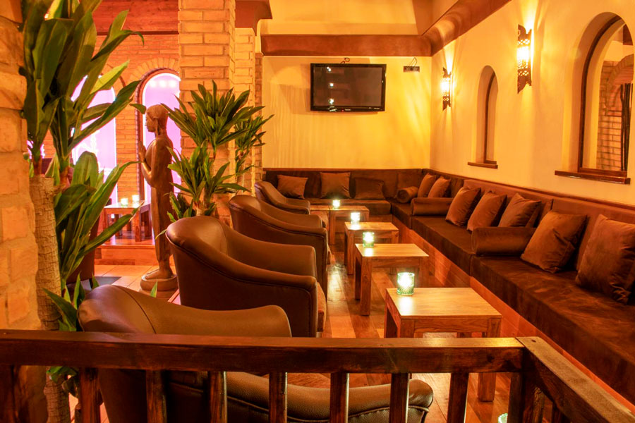 Salón con sofás, shishas, cachimbas, combinados y comida en Shisha o cachimba en el salón de Wooden Shisha Lounge Ibiza, tetería en Ibiza